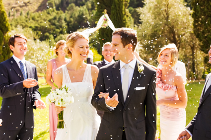 Guests Throwing Confetti On Couple During Garden Wedding